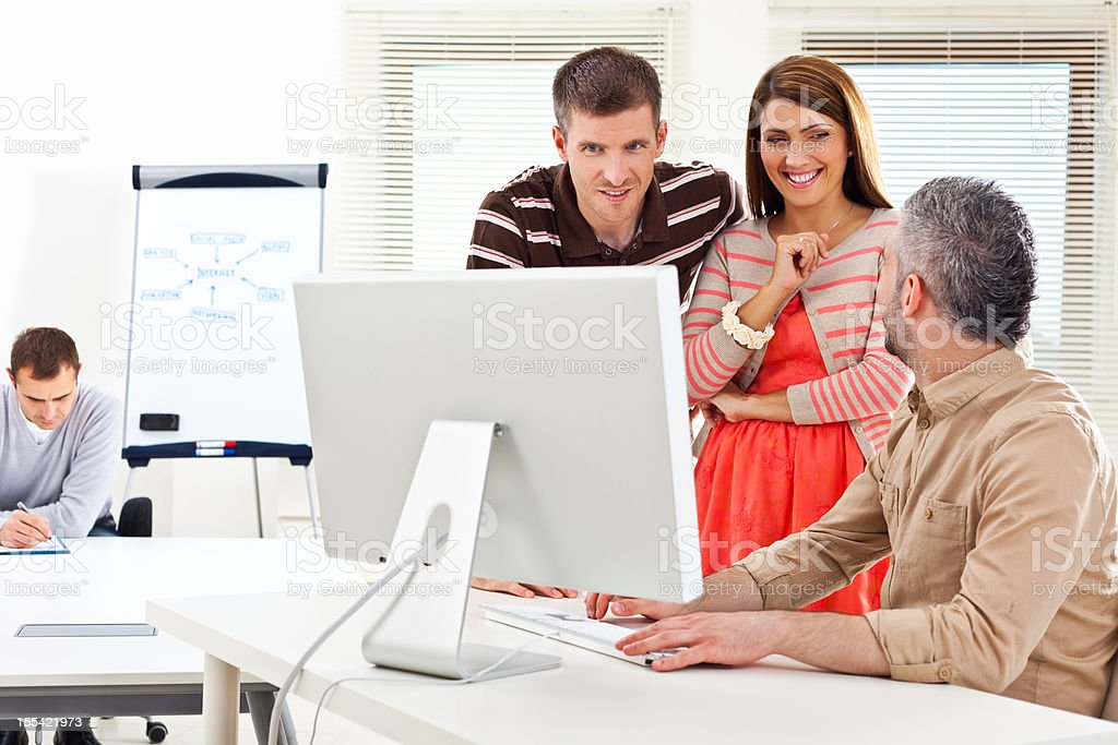 Teamwork Three colleagues discussing new project on the computer. 30-34 Years Stock Photo