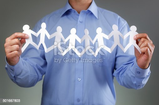 Teamwork, community and support concept with businessman holding paper chain group of people holding hands