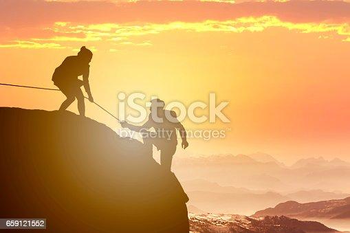 Teamwork on mountain peak