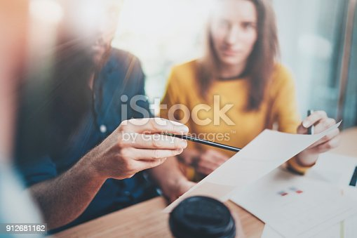 istock Teamwork process concept.Coworkers working at office.Closeup view of male hand pointing on paper document. Horizontal.Blurred background. 912681162