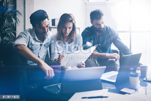 912675036istockphoto Teamwork process concept.Group of young coworkers work with new startup project in office.Horizontal, blurred background. 912611820