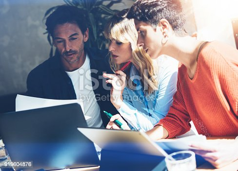 istock Teamwork process concept.Young coworkers team work with new startup project in office.Business people working at meeting room.Horizontal, blurred background. 919604876