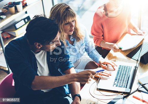 912675036 istock photo Teamwork process concept.Young coworkers team work with new startup project in office.Analyze document, plans.Modern laptop on wood table, papers, documents.Horizontal, blurred background. 919605372