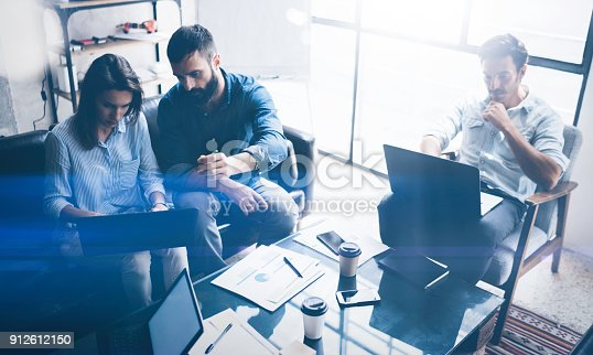 912617272 istock photo Teamwork process.Young coworkers work with new startup project in office.Modern laptop on table, papers, documents.Horizontal, blurred background. 912612150