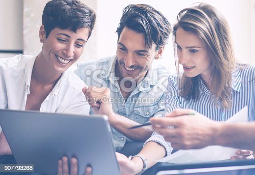 istock Teamwork process.Young entrepreneur work with new startup project in office.Woman holding touch pad in hands.Horizontal, blurred, flare 907793268