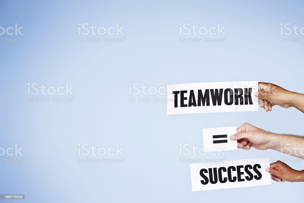 'Teamwork = Success' say hand-held words. Very true. stock photo