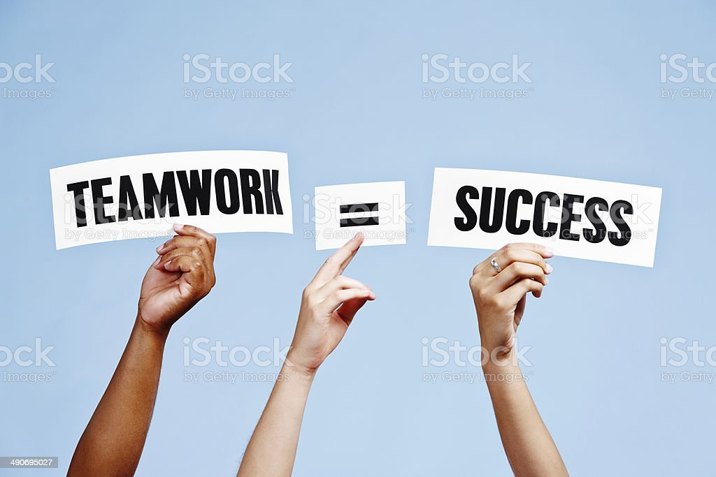 'Teamwork = Success' say hand-held words. Working together works! stock photo