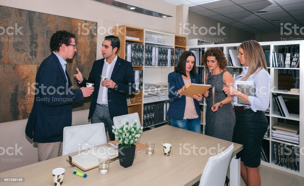 Teamwork talking after business meeting in office stock photo