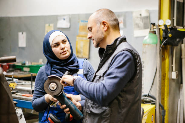 teamwork: technician explains a grinder to a female trainee in a workshop stock photo