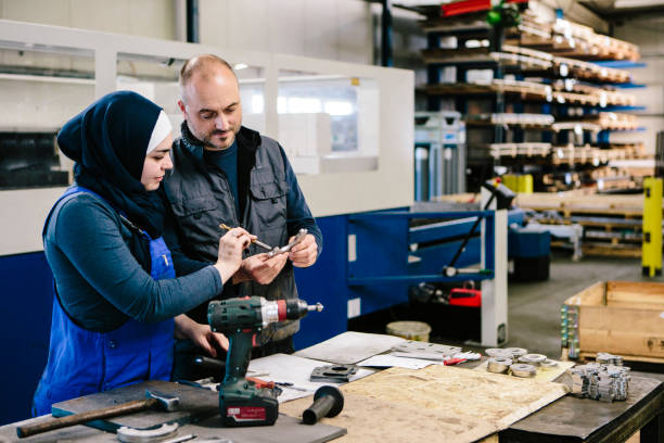 teamwork: technician explains a work tool to a young woman in a workshop stock photo