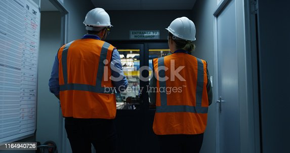 Rearview shot of two engineers walking through an industrial place of work