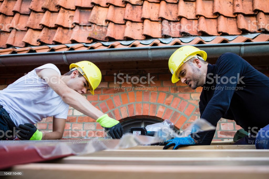 two worker on a roof of a carport next to a house