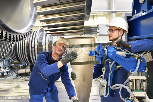 Teamwork - workers manufacturing steam turbines in an industrial factory