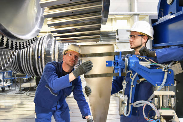 Teamwork - workers manufacturing steam turbines in an industrial factory Teamwork - workers manufacturing steam turbines in an industrial factory mechanical engineering stock pictures, royalty-free photos & images