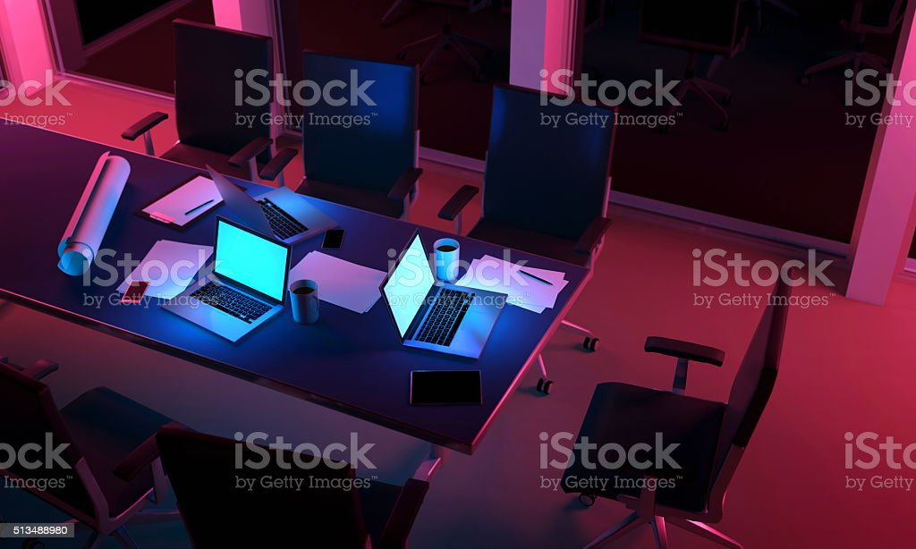Three laptop computers on a desk inside an office space at night,...