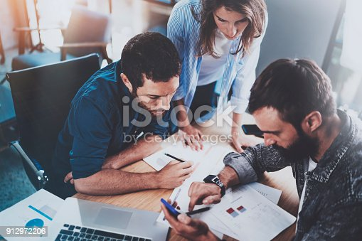 912969272istockphoto Teamwork working process.Group of young coworkers working together in modern office loft.Man using mobile phone.Blurred background.Horizontal. 912972206