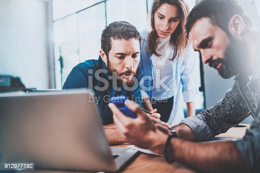 912969272istockphoto Teamwork working process.Group of young coworkers working together in modern office loft.Blurred background. 912977192