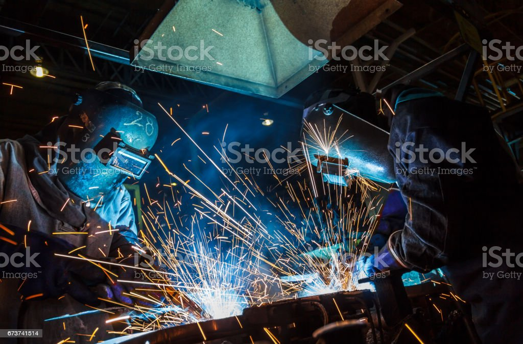 Teamworker with protective mask welding metal royalty-free stock photo