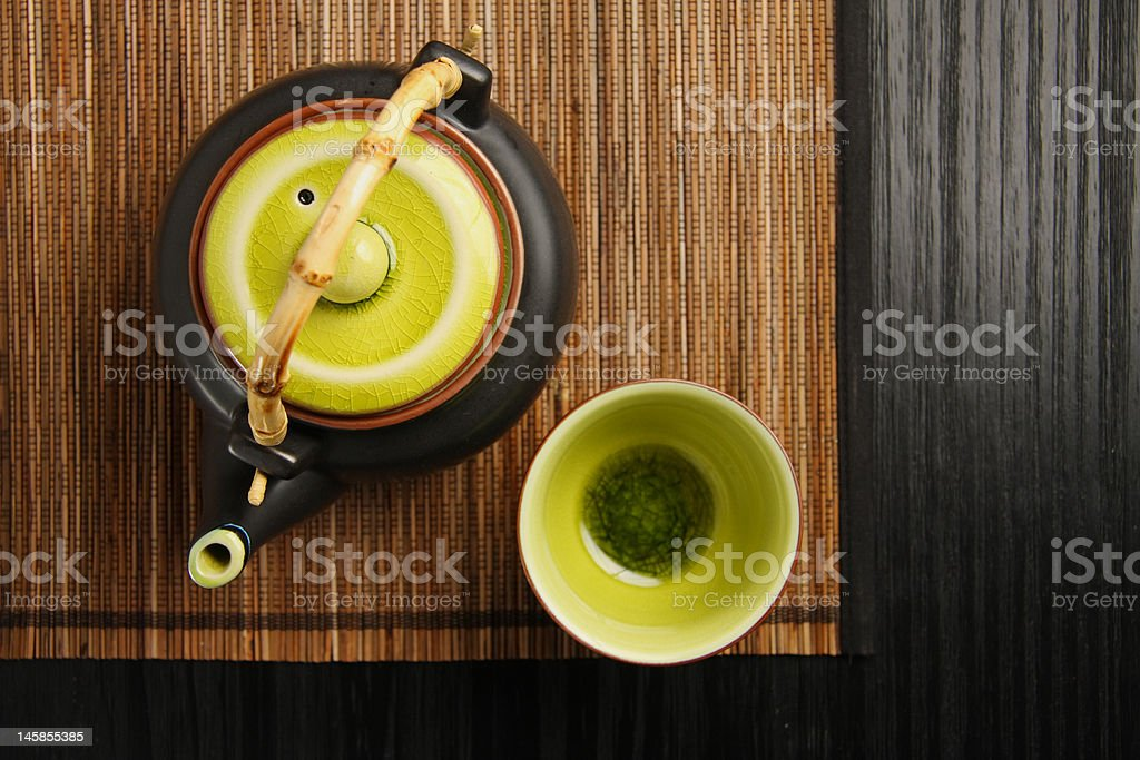 Teapot and cup on mat stock photo