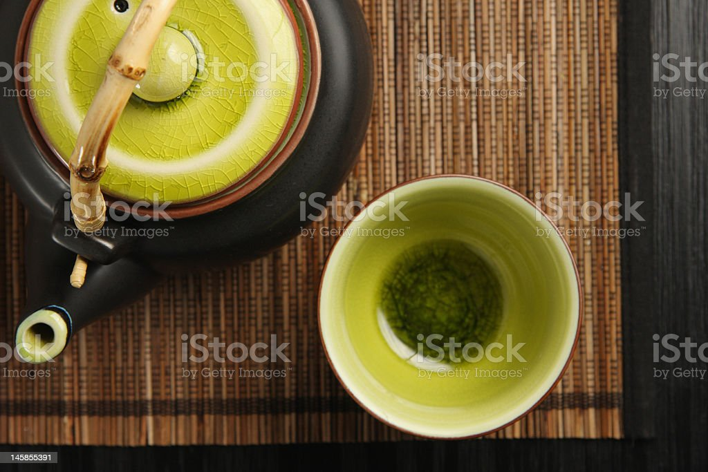 Teapot and cup on mat royalty-free stock photo