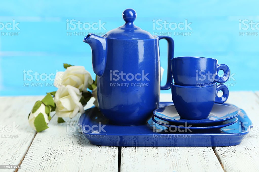 Teapot and cups on white wooden background stock photo