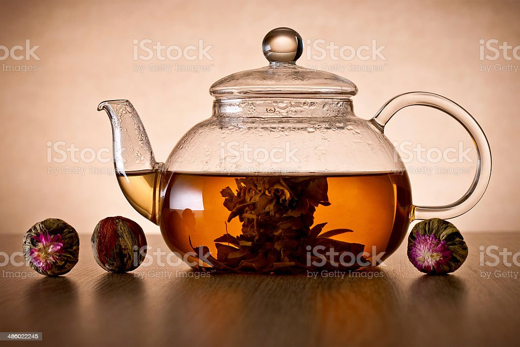 Teapot and glass cup with blooming tea flower. stock photo