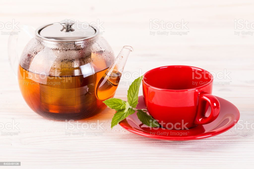 Teapot and red cup on wooden table stock photo