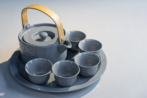 TeaPot ceramic set with New contemporary Modern and Vintage combination style on flat stone kitchen counter with sunlight from window.