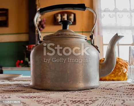 Photo of stainless steel kettle in neon light over red background. Steam from the kettle through the whistle.