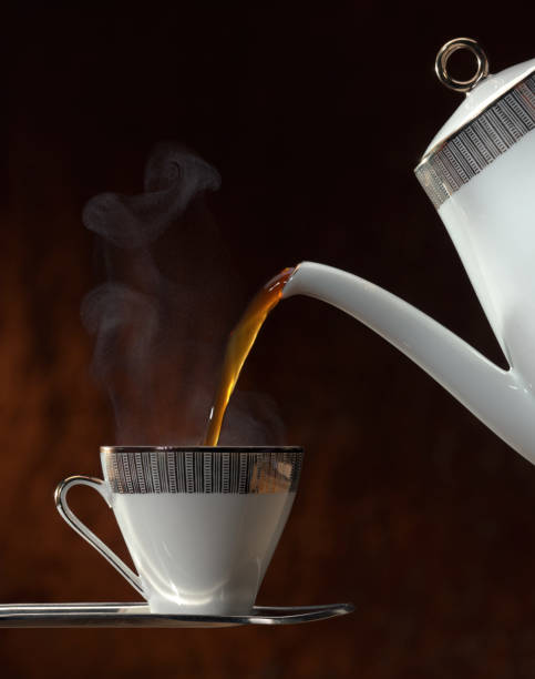 Teapot Pouring Hot Tea into Cup and Saucer stock photo