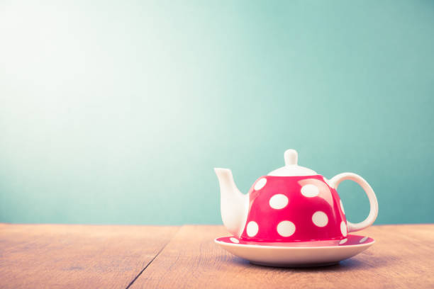 Teapot with polka dots on wooden table. Retro style filtered photo Teapot with polka dots on wooden table. Retro style filtered photo early 20th century stock pictures, royalty-free photos & images