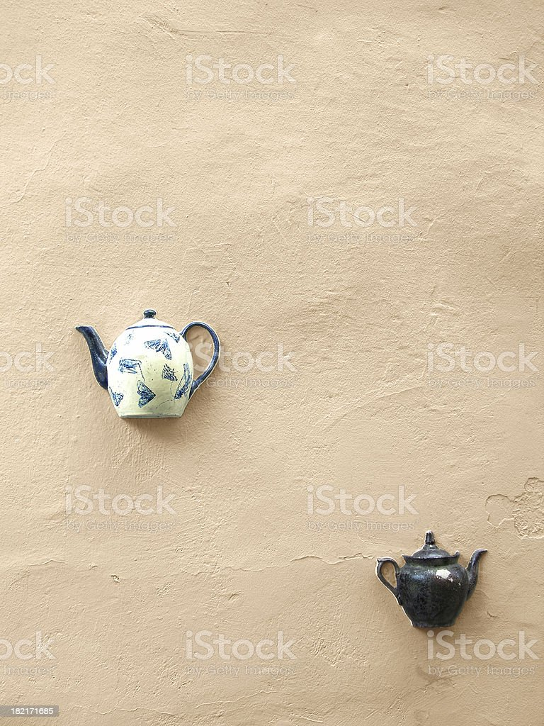 Teapots on wall, naturally royalty-free stock photo