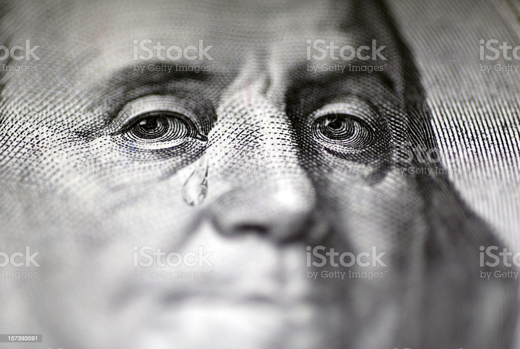 Tear falling from face on US dollar bill, close-up stock photo