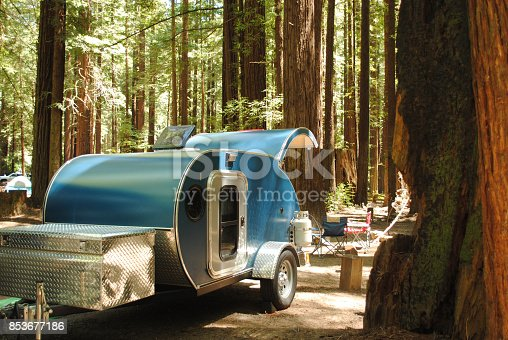 A blue teardrop camping trailer is setup at a campsite surrounded by redwood trees in Humboldt Redwoods State Park in California