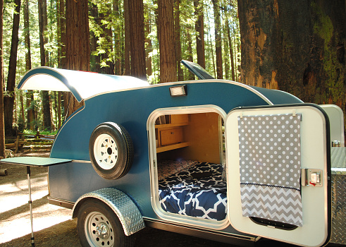 Blue teardrop camping trailer with doors open and view to interior, setup at a campsite surrounded by redwood trees in Humboldt Redwoods State Park in California