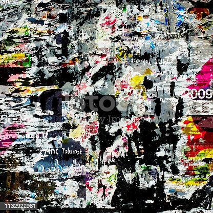 istock Teared off poster on the wall with colorful layers. 1132922961