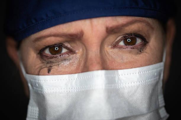 betraande beklemtoonde vrouwelijke arts of verpleegster die medisch gezichtsmasker op donkere achtergrond draagt - tears corona stockfoto's en -beelden