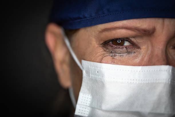 Tearful Stressed Female Doctor or Nurse Wearing Medical Face Mask on Dark Background stock photo