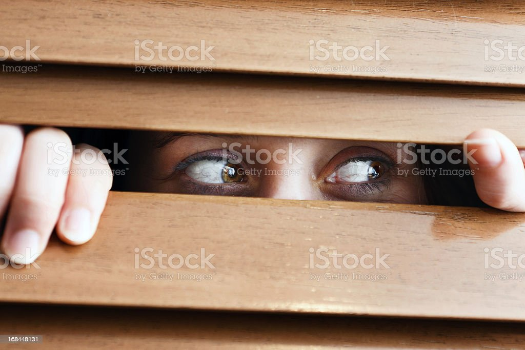 Tearful woman looks nervously sideways through venetian blind stock photo
