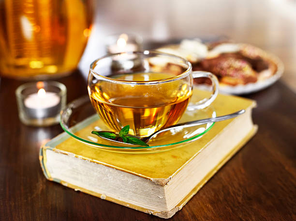 Teatime scene, cup of tea on a book stack Teatime scene, cup of tea on a book stack with burning candles and selective focus. tea room stock pictures, royalty-free photos & images