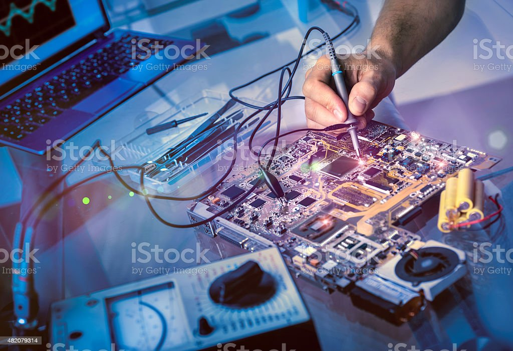 Tech fixes motherboard in service center stock photo