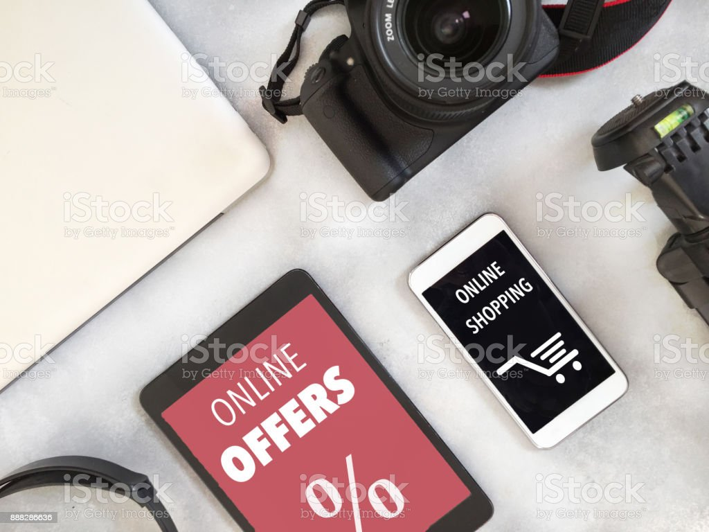 Tech items display and online offers text in English on devices stock photo