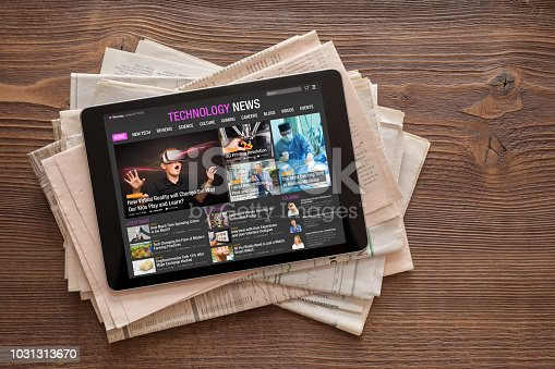 Close up photo of tech news website on tablet on stack of newspapers. All contents are made up.