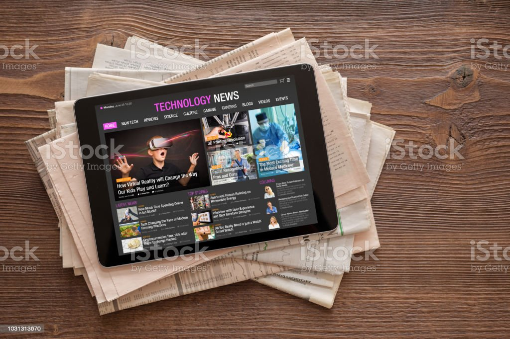 Tech news website on tablet on stack of newspapers. All contents are made up. stock photo
