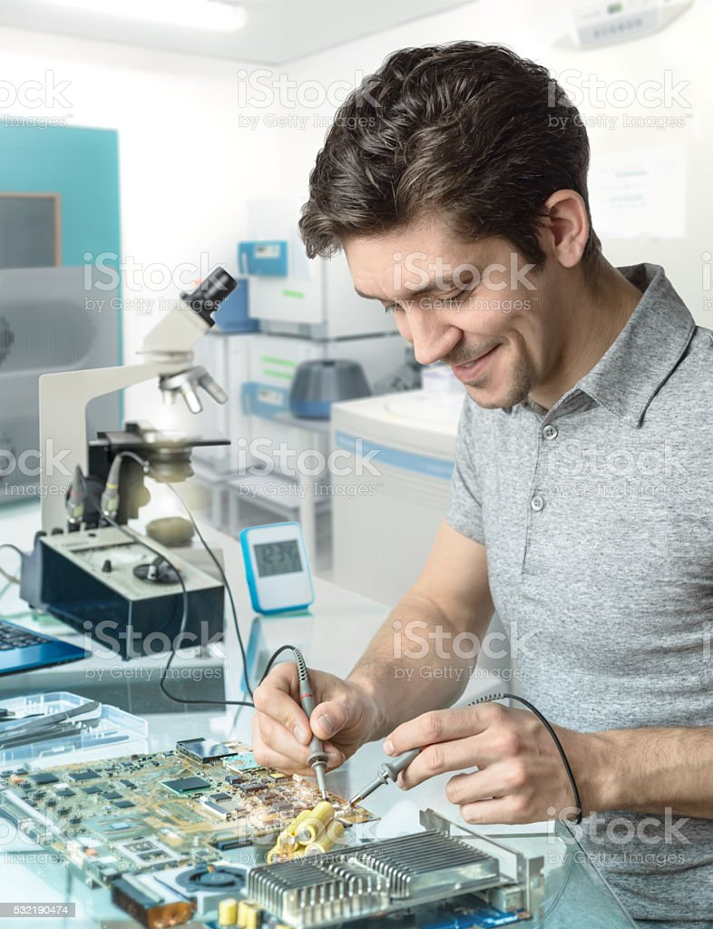 Tech or engineer repairs electronic equipment in research facili stock photo