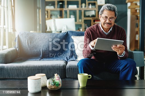Cropped shot of a mature man using his digital tablet while relaxing at home