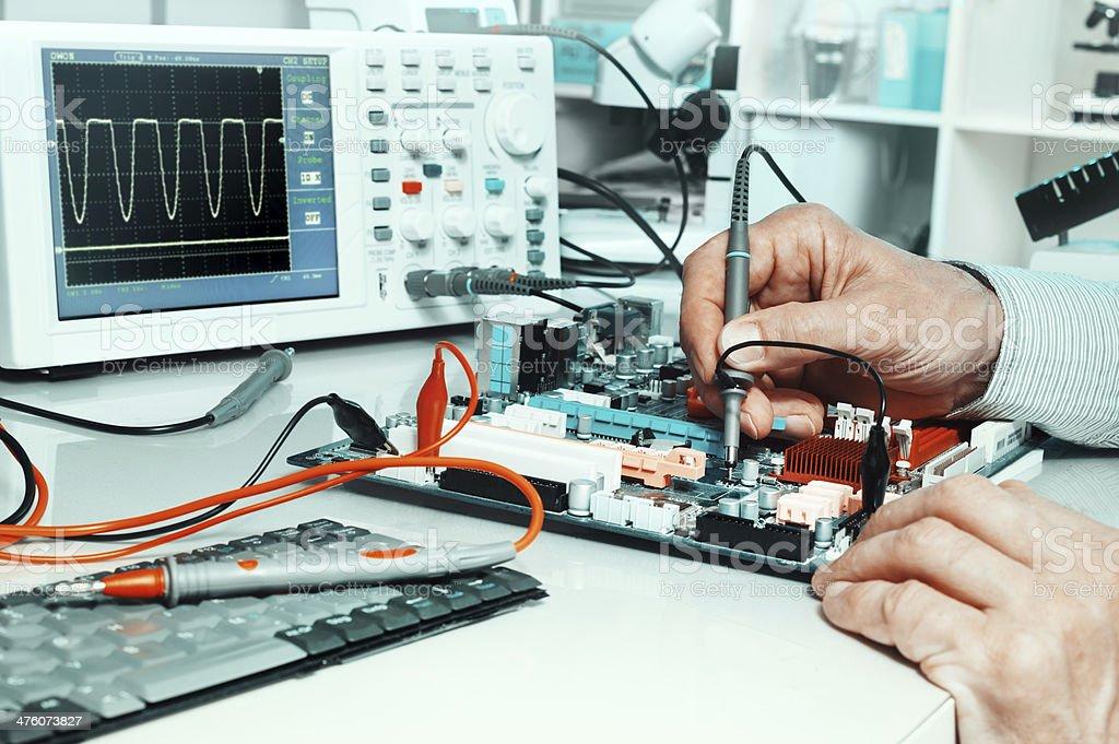 Tech tests electronic equipment stock photo