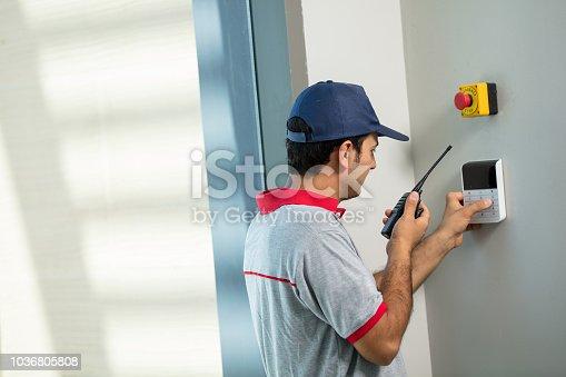 istock Techician set up security alarm 1036805808