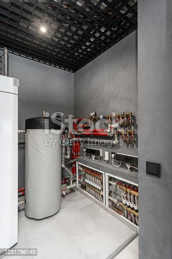Vertical photo of technical boiler room in new modern house with filter on water tank capacity, pipes equipment, plumbing stuff and valves on electronic counter meter