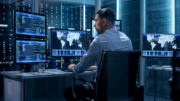 Technical Controller Working at His Workstation with Multiple Displays. Displays Show Various Technical Information. He's Alone in System Control Center. stock photo